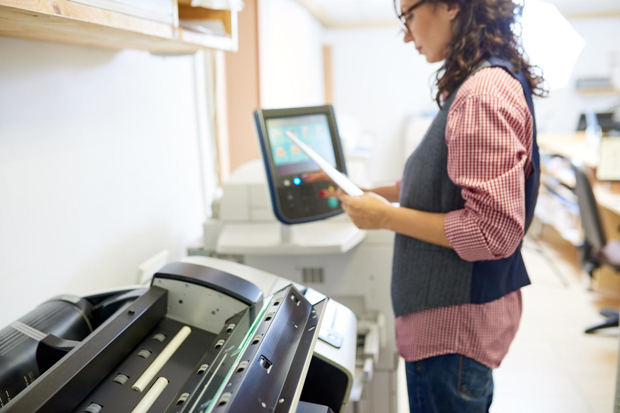 Woman adjusting settings on printer